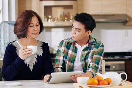 Son showing new application to mother 版權商用圖片