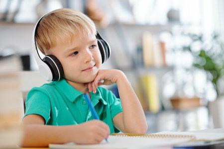 Cute schoolboy enjoying music