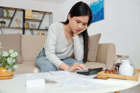 Stressed woman calculating expenses