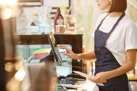 female barista using cash register