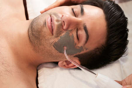 Young man relaxing with eyes closed when cosmetologist applying clay mask and doing ultrasound cleaning procedure with special device