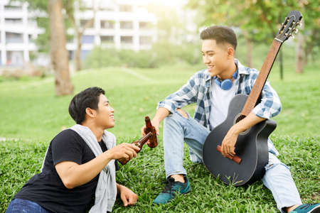 Two young men sitting on green grass with guitar and drinking beer outdoors Foto de archivo