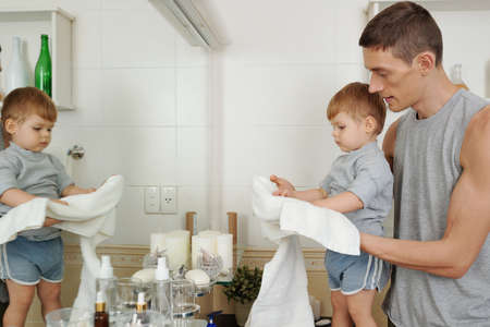 Young father teaching his little son to wipe his hands after washing in the morning in the bathroom 版權商用圖片