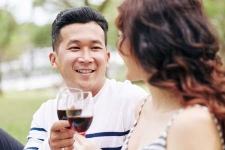 Portrait of smiling handsome young Asina man enjoying picnic with girlfriend and drinking wine