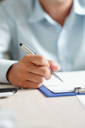 Close-up image of businessman sitting at office table and analyzing line chart on clipboard