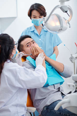 Dentist and nurse trying to reassure nervous patient scared of dental treatment Reklamní fotografie