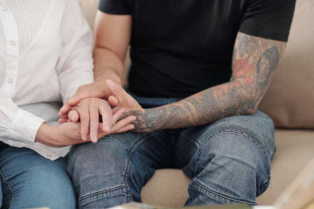 Hands of man with tattoed arms holding hands of his mature mother to reassure and support her