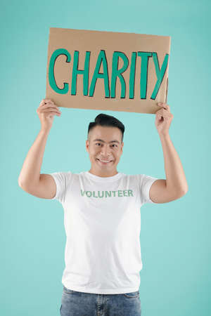Portrait of handsome smiling young Asian man holding placard with charity inscription and looking at camera Imagens