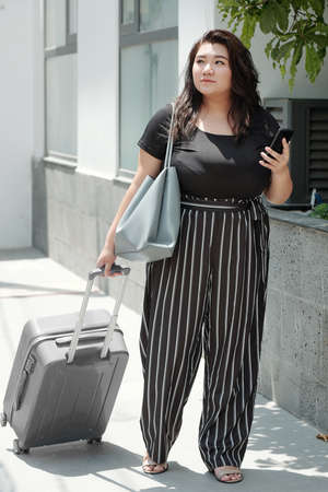 Pretty young woman in black t-shirt and striped pants walking with suitcase