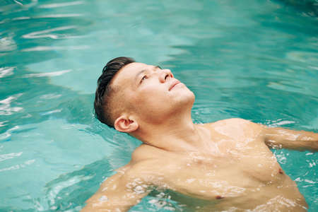Fit man floating on back in swimming pool and looking at sky