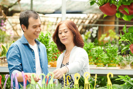 Mature woman and her adult son choosing plants and flowers in gardening center for house backyard