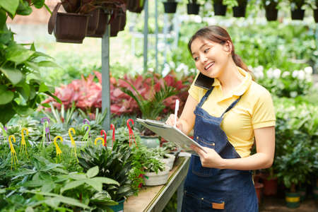 Smiling pretty gardening center worker talking on phone with customer and taking notes in document Stock Photo