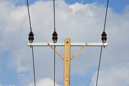 voltage gray: electricity post in blue sky Stock Photo