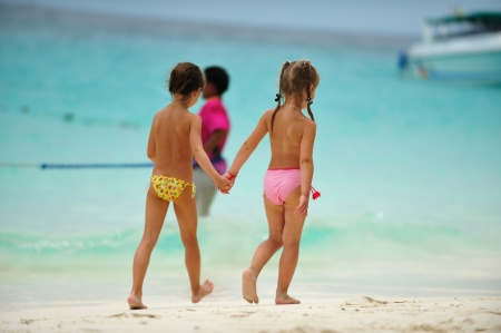 Two children walking hand in hand along the beach  Stock Photo