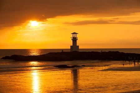 Lighthouse searchlight beam through marine at sunset.