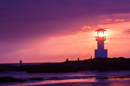 illuminative: Lighthouse searchlight beam through marine at sunset.