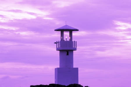 illuminative: Lighthouse searchlight beam through marine at sunset