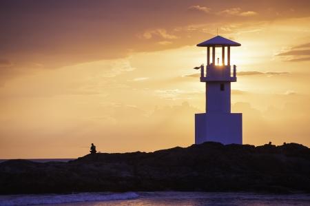illuminative: Lighthouse searchlight beam through marine at sunset
