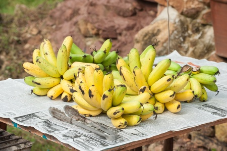 dainty: Bunch of Fresh dainty bananas on a banana leaf, wooden tray Stock Photo