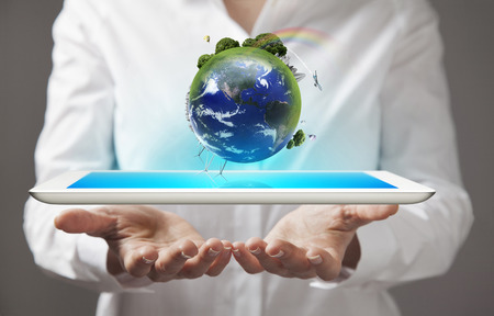 Young woman holding in her hands a tablet pc and earth globe photo