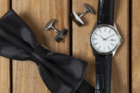 Directly above view of a old wooden table, bowtie cufflinks and wristwatch on it