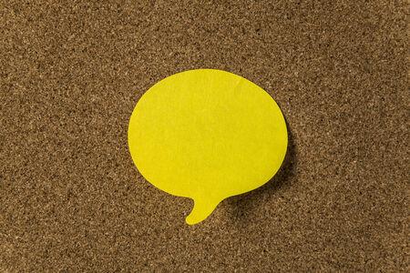 cork board: Yellow sticker with shape of speech bubble on cork board Stock Photo