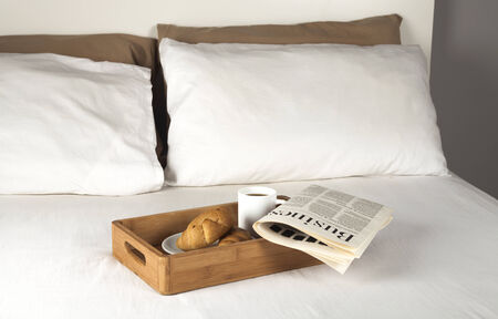 Breakfast tray and newspaper on a bed photo