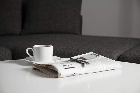 コーヒー カップとテーブルの上の新聞