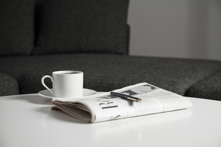 Coffee cup and newspaper on the table