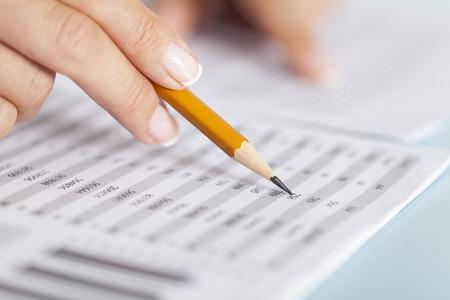 A hand checks part of a financial document