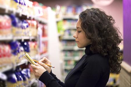 Woman checks her list in supermarket