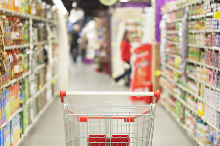 store shelf: Supermarket interior, empty red shopping cart.