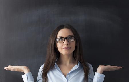 baffled: Portrait of confused businesswoman on blackboard Stock Photo