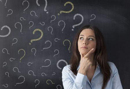 Businesswoman and question mark drawn in chalk on blackboard Standard-Bild