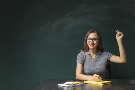 Portrait of young woman snapping fingers on blackboard