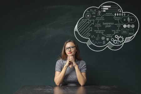 Woman contemplates business strategy thought bubble on chalkboard Banco de Imagens