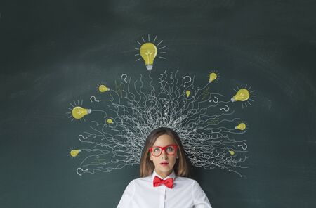 Thinking woman with lightbulbs drawing above head on blackboard background Banco de Imagens - 82872091