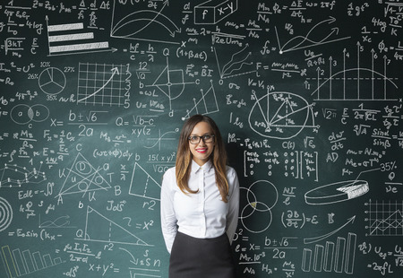 formula one: Businesswoman standing near blackboard with formulas and figures.