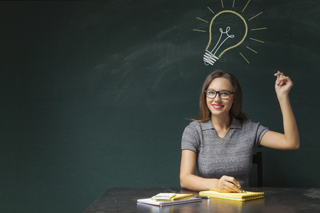 Young woman snapping fingers on board and light bulb over his head Stock Photo
