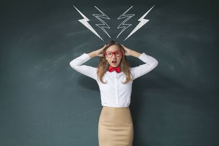 over voltage: Furious woman standing and shouting over drawn high voltage signs on chalkboard behind her