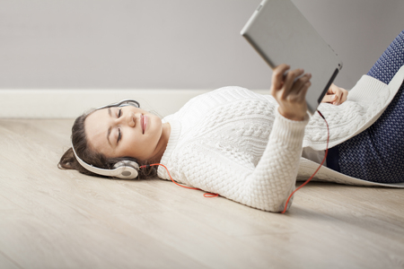 Cheerful young woman with headphones lying on floor at her home, using digital tablet.