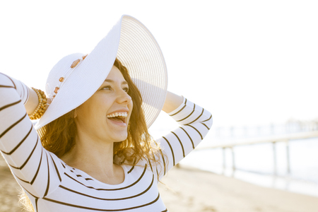 Close up portrait of young woman laughing with hat at the beach