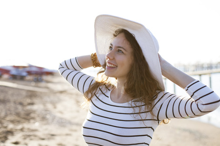 Close up portrait of young woman smiling with hat at the beach