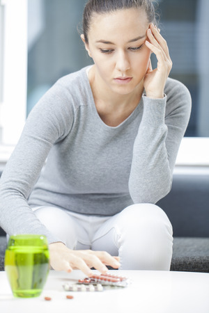 Stressed young woman in living room