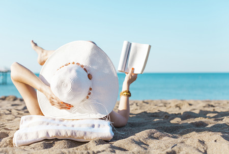Portrait of a young brunette relaxing on the beach, reading a book Stok Fotoğraf