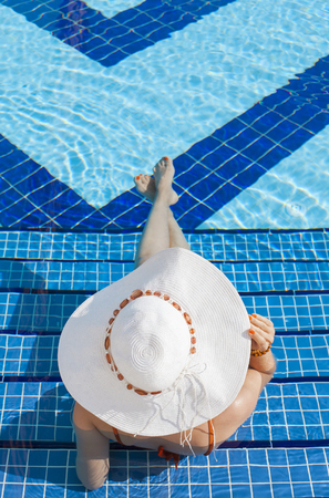 Woman with white hat relaxing in swimming pool in blue water Stock Photo