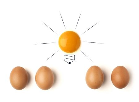 Egg yolk ball forming a shape of illuminated light bulb on isolated white background Stock Photo