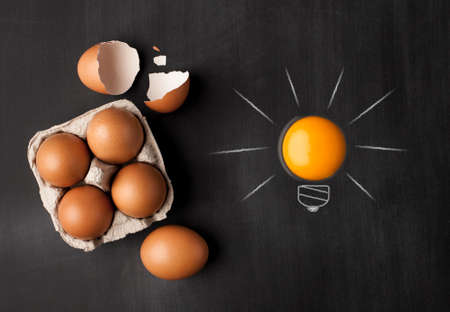 Egg yolk ball forming a shape of illuminated light bulb on blackboard Stock Photo