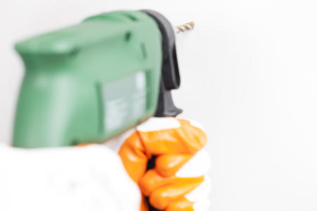 Handyman holding electric power driller, drilling hole in a white concrete wall