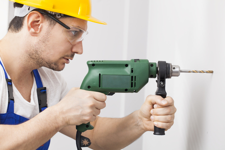 Young man using power drill on wall at home Stock Photo